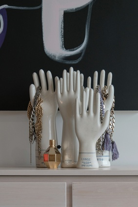 A group of vintage porcelain hands sits atop a dresser.