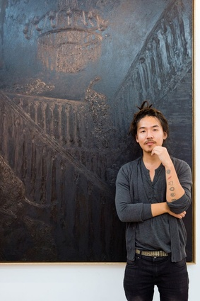 Artist Justin Lim at Richard Koh Fine Art Gallery in Bangsar Village with <em>Lux</em> (2015), a painting of dogs falling down a staircase – a commentary about wealth and status.