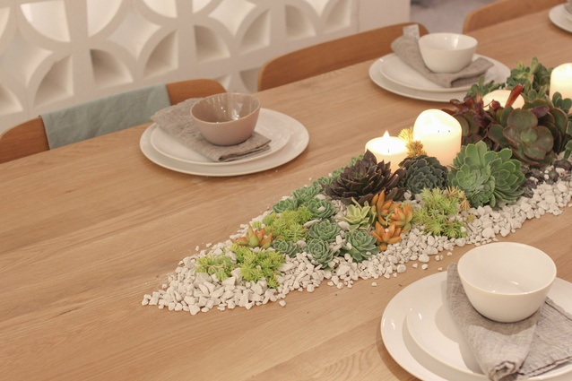 A table at the event decorated with plants and colours that inspired the collection.