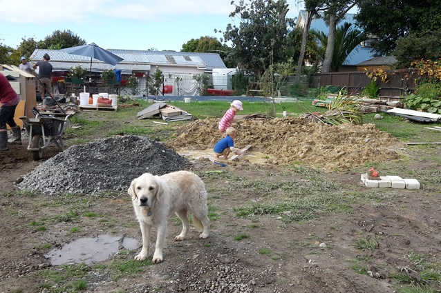 Evie Payne (the dog) on site with Isabelle & Nicolas working in the clay excavation pile from the ETS beds. Garry and Joel Payne in the background working on ramming the playhouse walls.