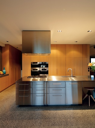 In the open-plan kitchen, the clean lines of the polished metal island and rangehood complement the light, contemporary look of the interior.