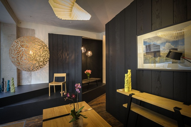 Painted black oak clads the walls to accentuate the warm tones of wooden furniture on display.