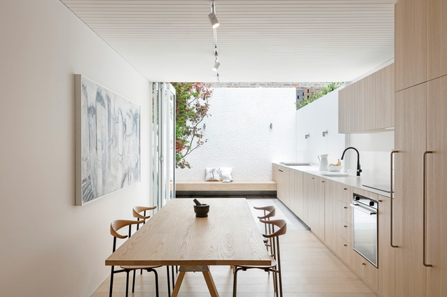 The kitchen extends seamlessly through bifold doors to a sunlit courtyard. Artwork: Mark Hanman.