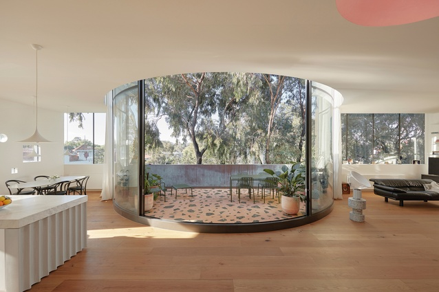 The penthouse's glazed, curved courtyard is stunning in the way it blurs the line between inside and out.