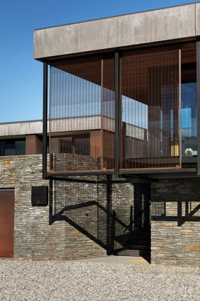 Schist, board-formed concrete and Corten steel provide the external material palette. 