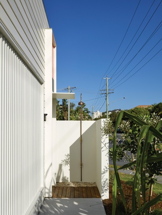 The entry to the home features an outdoor shower for rinsing off after visiting to the beach.
