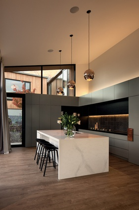 The kitchen has a high ceiling stud, and features copper pendants and large windows on two sides.