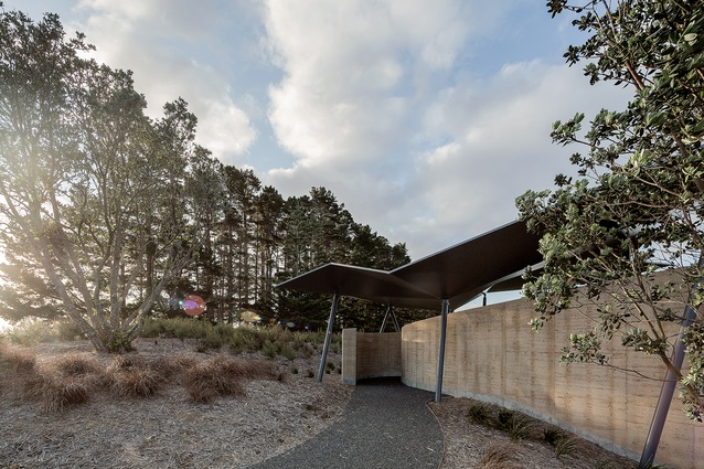 A loose-metal path leads you round the side of the building and through the curved, rammed-earth entrance.
