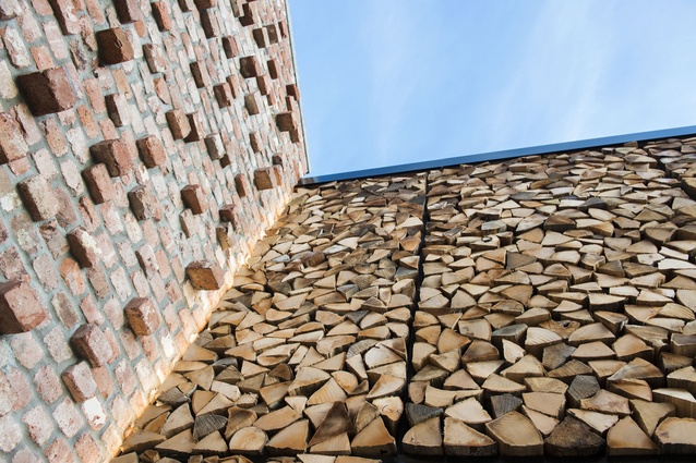 The textured wall surface of firewood and brick in the outdoor atrium.