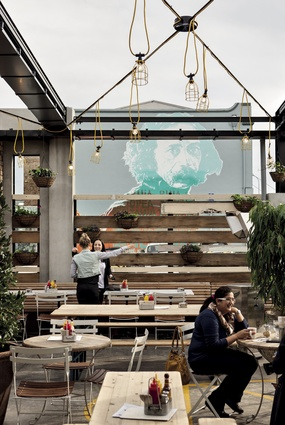 A mural of Ralph Hotere provides an impressive artistic backdrop to the well-planted outdoor area.