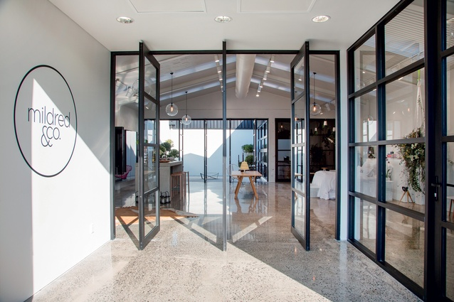 The entrance foyer, with series of black-framed pivoting doors. Similar doors open up to the small courtyard at the rear of the building.