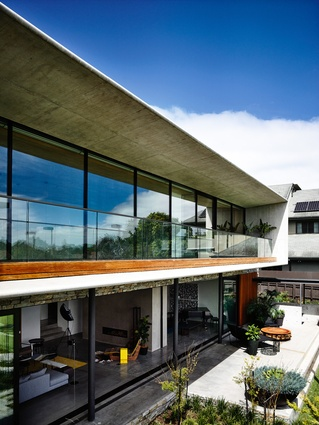 The rear of the home offers a verandah on the concrete-framed upper level and a planted court below.