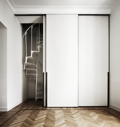 Sliding doors with minimalist and modern detailing hide a staircase leading to a small guest room.