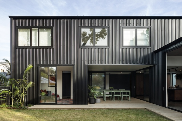 The house is clad in black metal, reminiscent of corrugated iron.