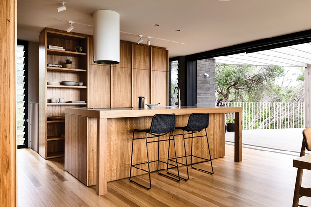 The timber kitchen island bench appears more as furniture than a functional cooking platform.