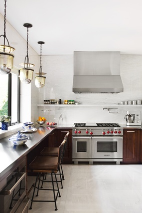 The kitchen features stainless-steel countertops and mahogany cabinetry.