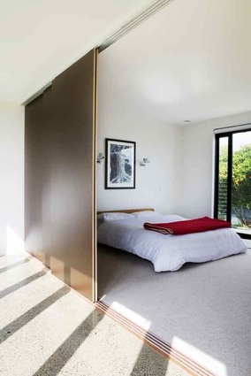 Large sliding doors let more light into this bedroom from the hallway.