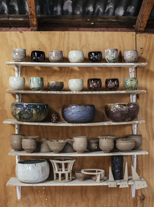 A range of Steer's pots displayed against the wooden walls of the studio.