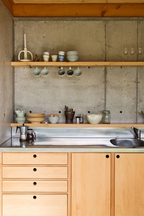 Kitchen of the Dogbox. A poured insitu concrete wall on the lower floor works both as thermal mass and as a retaining wall to the steep bank behind.