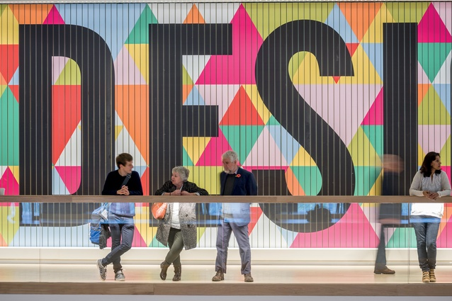 Visitors stand in front of a colourful permanent exhibition.