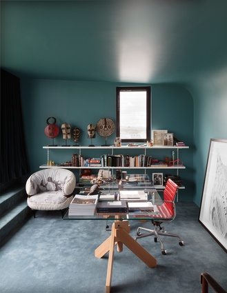 The study's teal-green walls offer a cocoon-like appearance, while personal effects and objects, including a mask collection from Africa, increase the cosiness factor.