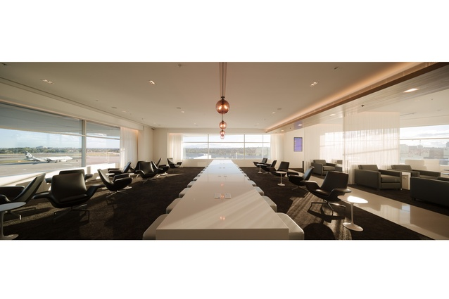 This business space in the Koru Lounge in Sydney airport features a communal table with integrated power and data ports. The signature violet color is used for the lights.