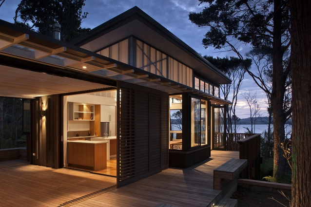 The modest Pahi Bach in Northland was built in 2012. Inserted between trees and wrapping around the path to the harbour edge, the home glows at night for maximum welcome.