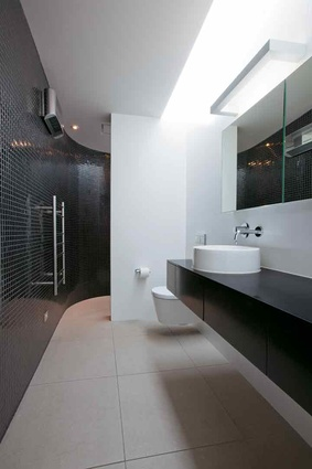 The glossy black tiles in the bathroom curve at one end into the shower area.
