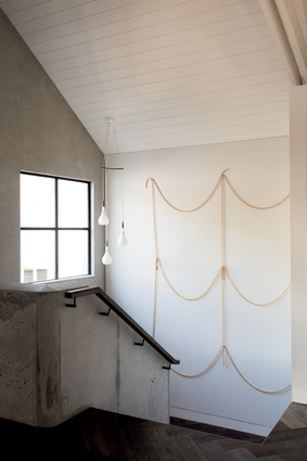 An artwork by Peter Robinson graces the stairwell leading up to the bedroom spaces.