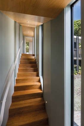 The corridor from the living spaces leads up a staircase to one of the bedrooms and features views over the internal courtyard to the right.