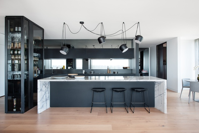 This dramatic kitchen retains a strong utilitarian presence, while still being connected to the penthouse's other areas.