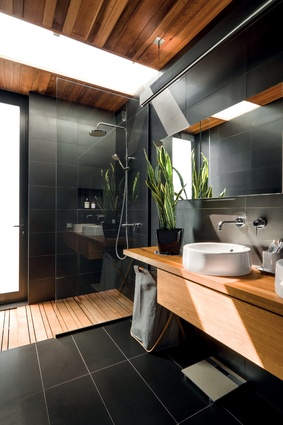 The main bathroom has a muted natural palette of materials. An external door will connect to a pool area when completed.