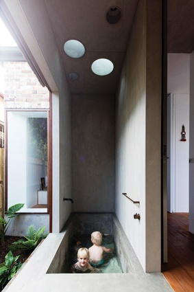 An in situ concrete bathtub scoops down in graceful, ergonomic lines, the space reminiscent of Japanese bathhouses.