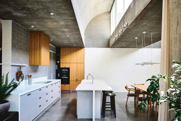 A wave-like concrete roof profile creates interest while allowing sunlight into the kitchen and living area.