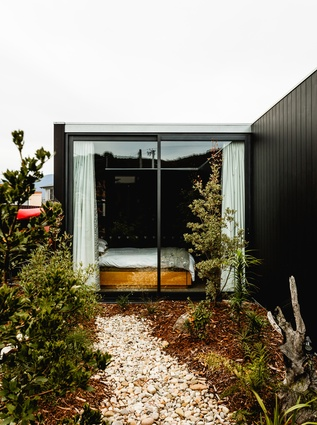In the bedroom, large sliding doors open onto the landscaped areas.