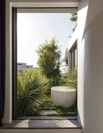 An outdoor bath sitting in the garden can be accessed from the en suite.