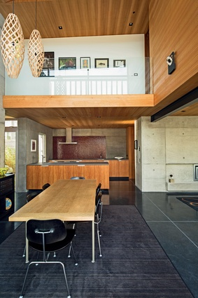 A house of shifting volumes and demarcated spaces, the double-height dining area affords a glimpse of the upper level.