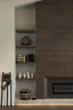 The fireplace is clad in Neolith ceramic tiles in Iron Corten, which gives a rustic aesthetic to the space. Floating shelves provide storage on either side of the chimney, which also conceals a TV.