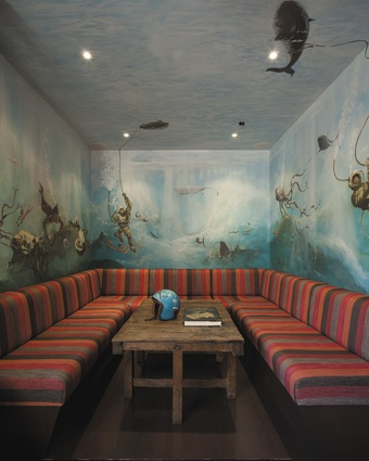 A booth with underwater mural and colourful linen seating provides a visual high-point within the woody interior.