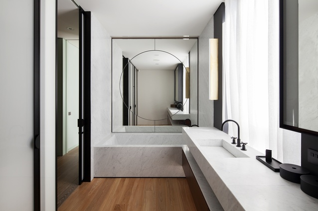 A Michael Anastassiades Tube wall light can be seen in the bathroom.