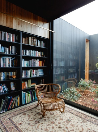 Part of the client's brief was that the house should make space for a collection of antique books, the same which influenced the overall design of the building. The library looks out onto one of the four courtyards.