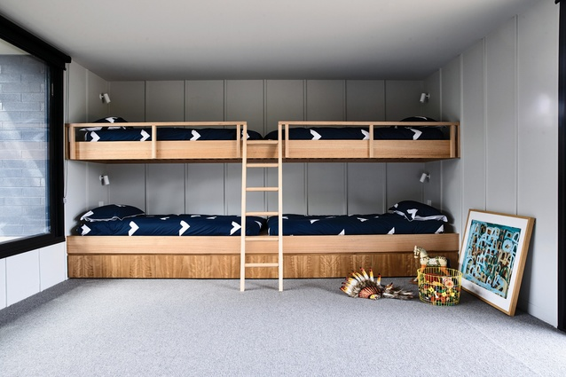 In the kids' bedroom, top-to-toe bunk beds with integrated storage are pushed to the end wall, so the rest of the space can be used as a playroom. Artwork: Warren O'Brien.