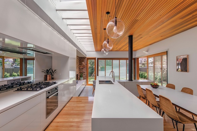 A strip of polycarbonate skylight running above the kitchen and living area increases the sense of volume and height.